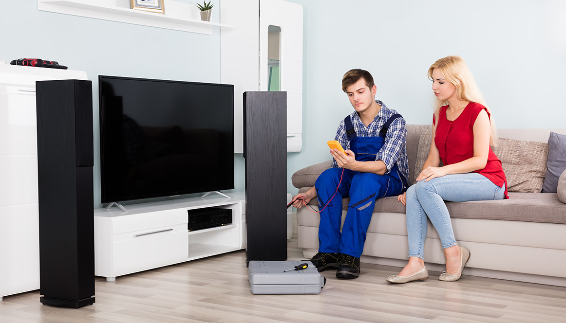 Man installing speakers in a livingroom with a woman observing
